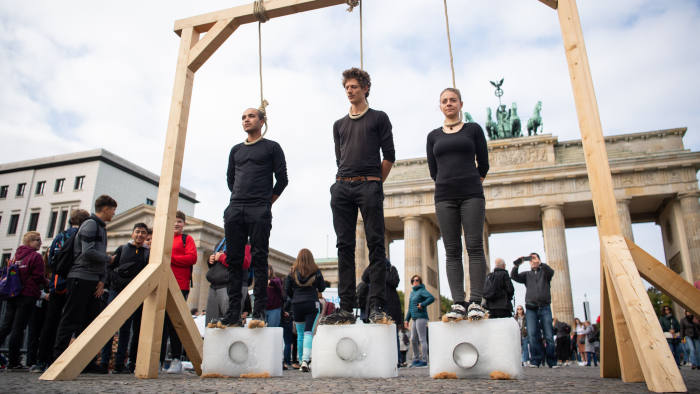 20 September 2019, Berlin: Activists stand on blocks of ice with ropes around their necks on gallows backdropped by the Brandenburg Gate during a protest calling for more action to help stop climate change. Photo: Tom Weller/dpa