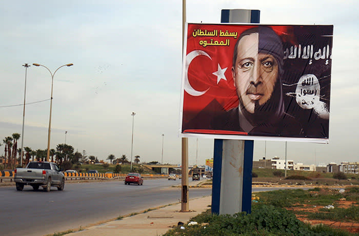 A picture taken on February 13, 2020 shows a billboard depicting the Turkish President Recep Tayyip Erdogan as a member of the Islamic State (IS) group the in the eastern Libyan port city of Benghazi. (Photo by Abdullah DOMA / AFP) (Photo by ABDULLAH DOMA/AFP via Getty Images)