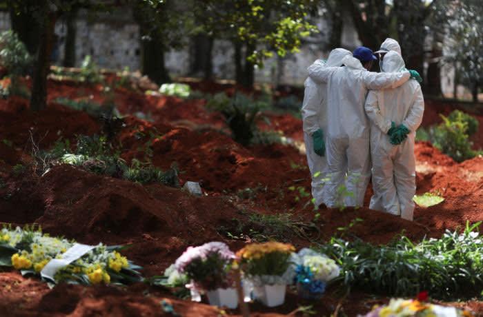 Gravediggers wearing protective suits gather at Vila Formosa cemetery, Brazil's biggest cemetery, during coronavirus disease (COVID-19) outbreak, in Sao Paulo, Brazil, April 2, 2020. REUTERS/Amanda Perobelli