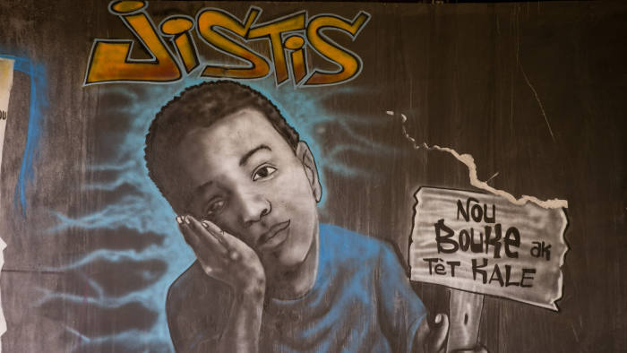 "In this Feb. 12, 2020 photo, a mural shows a child with a sign that says in Creole: ""We are tired of the shaved head,"" and ""Justice,"" painted under a bridge that was built with money from the now-defunct Venezuelan PetroCaribe program, in Port-au-Prince, Haiti. The slogan is used against Haitian President Jovenel Moise, who has a shaved head, and the bridge became a meeting point for deadly anti-government protests. (AP Photo/Dieu Nalio Chery)"