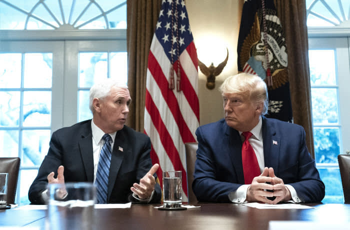 U.S. Vice President Mike Pence speaks while U.S. President Donald Trump, right, listens during a meeting with the Coronavirus Task Force and pharmaceutical executives in the Cabinet Room of the White House in Washington, D.C., U.S. on Monday, March 2, 2020. Executives told Trump they were making rapid progress on vaccines and antivirals to combat the coronavirus, which has infected about 100 people in the country and killed six. Photographer: Kevin Dietsch/UPI/Bloomberg