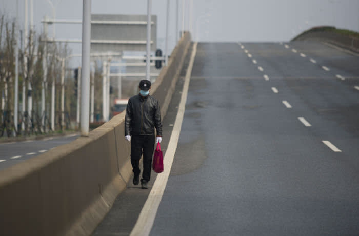 TOPSHOT - A man walks on an empty street in Wuhan, in China's central Hubei province on February 29, 2020. - Wuhan's 11 million resident have been under effective quarantine since January 23 as Chinese authorities race to contain the COVID-19 coronavirus outbreak. (Photo by STR / AFP) / China OUT (Photo by STR/AFP via Getty Images)
