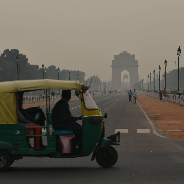 An auto-rickshaw drives past India Gate on a smoggy morning in New Delhi on 6th November, 2019. Air pollution in New Delhi and surrounding towns reached the worst levels so far this year declarinng a public health emergency.