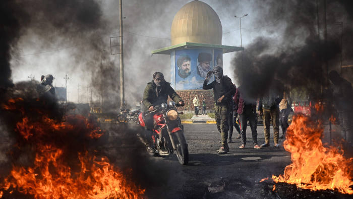 An Iraqi anti-government protester rides his motorcycle as burning tires block a road leading to the airport in the Iraqi holy city of Najaf on January 21, 2020. - Rallies have rocked Iraq since October but, fearing they would lose momentum amid spiralling regional tensions, protesters told the government it had one week to meet their demands or they would escalate their demonstrations. (Photo by Haidar HAMDANI / AFP) (Photo by HAIDAR HAMDANI/AFP via Getty Images)