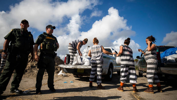 Mandatory Credit: Photo by JIM LO SCALZO/EPA-EFE/Shutterstock (10376718k) Female inmates from Brevard County Jail load free sandbags into the trunk of resident's car in Cocoa, Florida, USA, 01 September 2019. Hurricane Dorian, a powerful Category 5, is expected to strike the Bahamas on Sunday 01 September before passing to the east of Florida early next week. Floridians prepare for Hurricane Dorian, Cocoa, USA - 01 Sep 2019