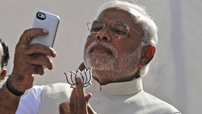 Narendra Modi...FILE- In this April 30, 2014 file photograph, India's main opposition Bharatiya Janata Party's prime ministerial candidate Narendra Modi holds his party's symbol and looks into his phone after casting his vote in Ahmadabad, India. In the Twitterverse ruled by President Barack Obama, India's new Prime Minister Modi may soon overtake the White House on Twitter.An analysis of Twitter accounts — showing the emphasis some governments put on digital diplomacy as a 21st-century tool for statecraft — projects Modi, already the fifth most-followed world leader on Twitter with 4.95 million followers, will soon overtake the White House's 4.97 million.(AP Photo/Ajit Solanki, file)