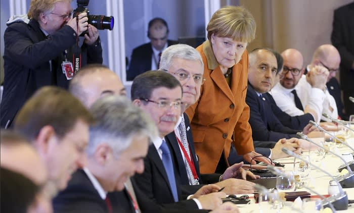 Angela Merkel lunching with Turkish PM Ahmet Davutoglu (on her right, blue tie) in March 2016, during a summit called to tackle the EU's migration crisis; her proposed solution was to make Turkey a 'safe country'