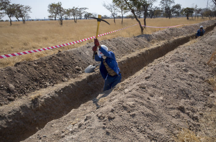 A municipal worker digs a trench to prepare for the laying of a new water pipe along Khami Road in Bulawayo, Zimbabwe, on Friday, Aug. 2, 2019. Zimbabwe is in the grip of a nationwide drought that's depleted dams, cut output by hydropower plants, caused harvests to fail and prompted the government to appeal for $464 million in aid to stave off famine. Photographer: Cynthia R Matonhodze/Bloomberg