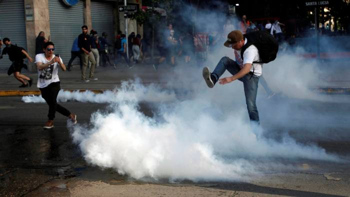 A demonstrator kicks a tear gas canister during a protest against the increase in the subway ticket prices in Santiago, Chile, October 18, 2019 REUTERS/Carlos Vera NO RESALES. NO ARCHIVES