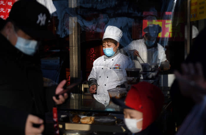 A restaurant worker wears a face mask as a preventive measure against the COVID-19 coronavirus as she serves customers through a window in Beijing on March 3, 2020. - The world has entered uncharted territory in its battle against the deadly coronavirus, the UN health agency warned, as new infections dropped dramatically in China on March 3 but surged abroad with the US death toll rising to six. (Photo by GREG BAKER / AFP) (Photo by GREG BAKER/AFP via Getty Images)