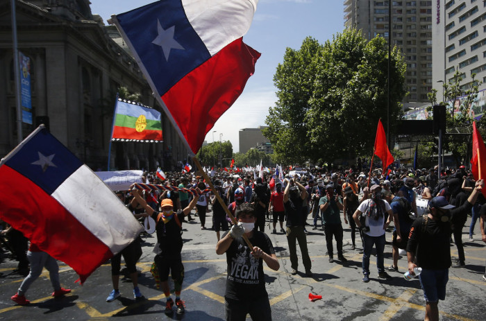 SANTIAGO, CHILE - OCTOBER 23: Demonstrators wave flags of Chile during the sixth day of protest against President Sebastian Piñera on October 23, 2019 in Santiago, Chile. Although President Sebastian Piñera announced yesterday a few measures to improve equality, unions called for a national strike and demonstrations continue as casualties are now 18. Demands behind the protest include issues like health care, pension system, privatization of water, public transport, education, social mobility and corruption. (Photo by Marcelo Hernandez/Getty Images)