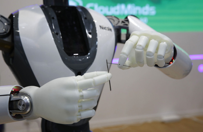 A humanoid robot called 'Nicole' threads a needle on the CloudMinds Technology Inc. stand on the opening day of the MWC Barcelona in Barcelona, Spain, on Monday, Feb. 25, 2019. At the wireless industry's biggest conference, over 100,000 people are set to see the latest innovations in smartphones, artificial intelligence devices and autonomous drones exhibited by more than 2,400 companies. Photographer: Stefan Wermuth/Bloomberg