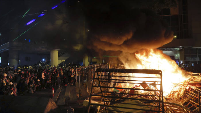 FILE - In this Aug. 31, 2019. file photo, fire caused by protesters and others is seen during a pro-democracy protest in Wan Chai, Hong Kong. Hong Kong's Apple Daily newspaper says the outspoken head of its publishing group, Jimmy Lai, has been held by police Friday, Feb. 28, 2020 over his participation in the protest march that was part of a months-long pro-democracy movement. (AP Photo/Kin Cheung, File)