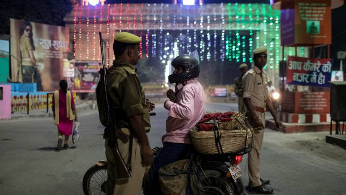 A police officer checks identity papers at a checkpoint, after Supreme Court's verdict on a disputed religious site, in Ayodhya, India, November 10, 2019. REUTERS/Danish Siddiqui