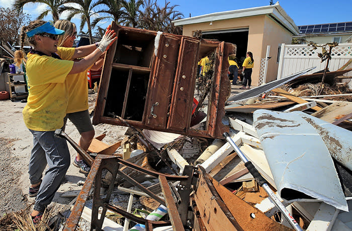 Maria Stotts and Heather Mueller, volunteers from the Church of Jesus Christ of Latter-Day Saints, clear debris from a Monroe County sheriff's deputy home damaged by a 6-foot storm surge at his home, far West in Big Pine Key. Residents were allowed to return to their homes in the Keys today a week after Hurricane Irma struck the Florida Keys. (Al Diaz/Miami Herald/Tribune News Service via Getty Images)