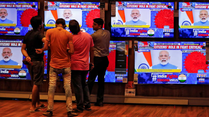 People watch Indian Prime Minister Narendra Modi addressing the nation amid concerns about the spread of coronavirus disease (COVID-19), on TV screens inside a showroom in Ahmedabad, India, March 19, 2020. REUTERS/Amit Dave