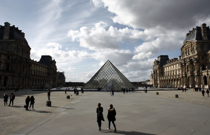 FILE - In this March 13, 2020 file photo, people walk by the Louvre Museum, in Paris. Iconic sites that are among some of France's biggest tourist draws won't reopen when the country lifts most of its coronavirus restrictions next week. Neither the Louvre Museum, the Eiffel Tower nor the Versailles Palace will be reopening next week when France lifts many of its remaining coronavirus lockdown restrictions. (AP Photo/Thibault Camus, File)