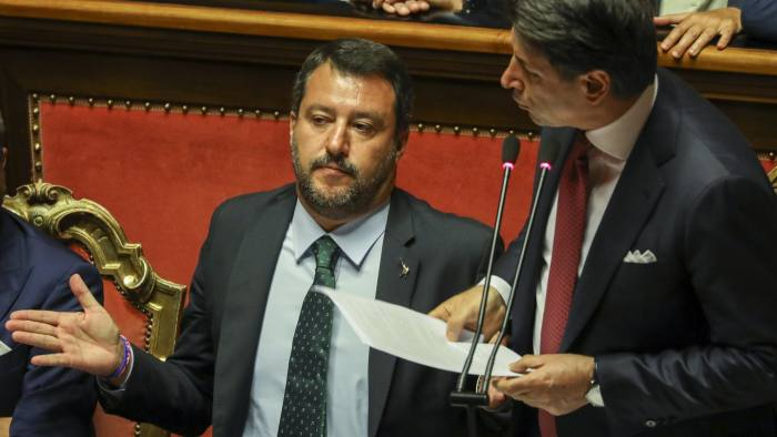 Matteo Salvini, Italy's deputy prime minister, left, gestures as Giuseppe Conte, Italy's prime minister, addresses the Senate in Rome, Italy, on Tuesday, Aug. 20, 2019. Salvini dangled the prospect of tax cuts and a boost in government spending for Italians in a final push to force new elections that could secure him the premiership. Photographer: Alessia Pierdomenico/Bloomberg