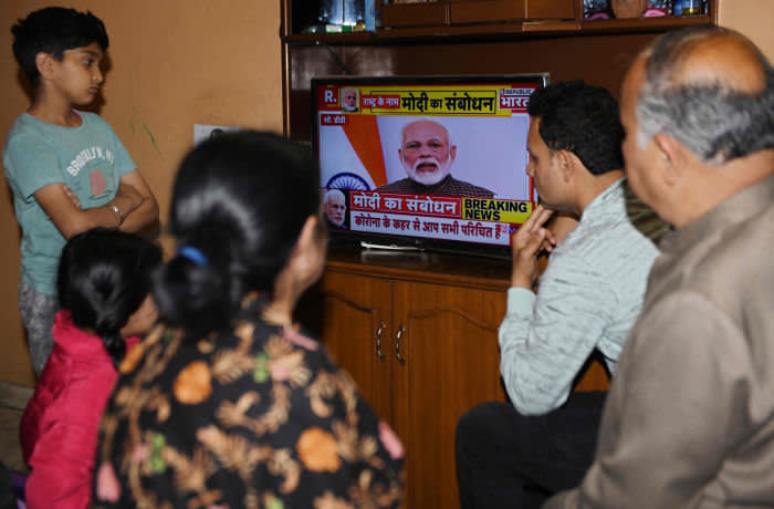 """A familywatches Indian Prime Minister Narendra Modi's address to the nation on a television set on a television at their home in Amritsar on March 24, 2020. - India's 1.3 billion people will go under """"total lockdown"""" from midnight on March 24 (1830 GMT) for 21 days to combat the spread of the coronavirus pandemic, Prime Minister Narendra Modi said. """"From 12 midnight today, the entire country will be in lockdown, total lockdown,"""" Modi said in a national television address to the world's second most-populous nation. (Photo by NARINDER NANU / AFP) (Photo by NARINDER NANU/AFP via Getty Images)"""