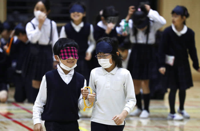 Students of Ariake-nishi Gakuen School wear protective face masks, following the outbreak of the coronavirus, as they attend an event Six Months to go until Tokyo 2020 Paralympic Games in Tokyo, Japan, February 25, 2020. REUTERS/Athit Perawongmetha - RC2M7F9MPZBR