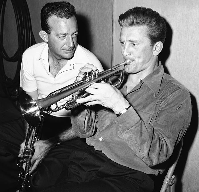 Harry James (left), whose trumpet playing rates among the best, here shows Kirk Douglas how to toot for the movie cameras on July 12, 1949 in Hollywood, Calif. The tooting-tutoring is in preparation for Douglas?s role as a great trumpet player in ?Young man with a horn.? (AP Photo)