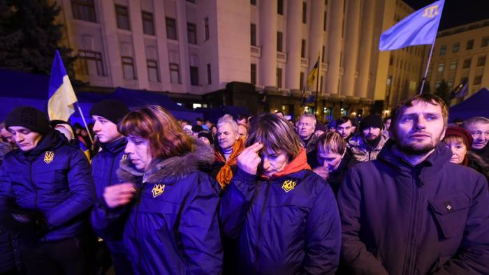 People gather outside the presidential office in Kiev on December 9, 2019 as they wait for the results of a summit on the conflict in Ukraine's east with Putin, Zelensky, Macron and Merkel held in Paris. (Photo by SERGEI SUPINSKY / AFP) (Photo by SERGEI SUPINSKY/AFP via Getty Images)