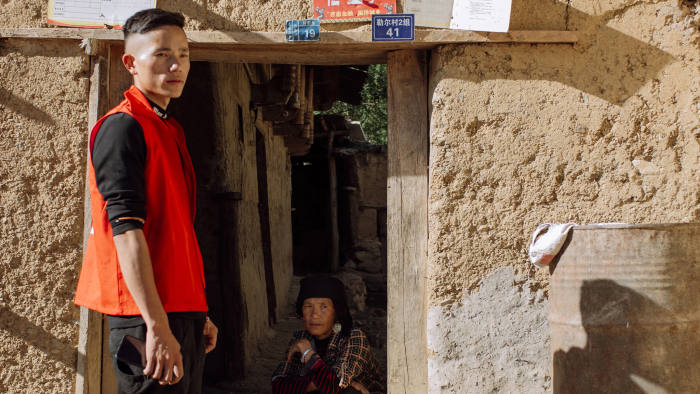 """Jike Shibu (24) and his mother Afu Miji (56) in front of their house in the second group of the Atulie'er village, May 18 2020. Placed on the lintel are low income family assistance cards of 2019 and 2020, """"credit family"""" certificate from the Liangshan Rural Commercial Bank and a certificate that writes """"Four-Good Star Family""""."""