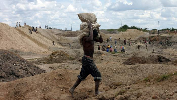 File photo of a Congolese man carrying bags of copper and cobalt ore at an open-pit mine just outside Lubumbashi...A Congolese man carries bags of copper and cobalt ore at an open-pit mine just outside the southern Congolese copper town of Lubumbashi in this February 3, 2006 file photo. The mine used to be run by Gecamines. Congo's debt-ridden state mining company Gecamines needs to cut almost half its 12,000 workforce and find hundreds of millions of dollars to fund a rebuilding programme, its new manager said. Picture taken on February 3, 2006.REUTERS/David Lewis/Files - RTR15X48