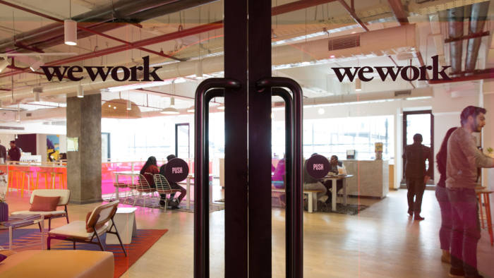 Signage is displayed on glass doors at the WeWork Cos. 32nd Milestone co-working space in Gurugram, India, on Monday, Feb. 18, 2019. The New York-based co-working giant WeWork Cos, which operates shared office spaces around the world, has attracted huge piles of investor money, which it uses to snap up office space in the largest cities on earth. Photographer: Ruhani Kaur/Bloomberg