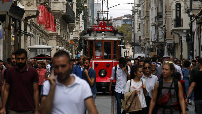 People walk in Istiklal Avenue, the main shopping road of Istanbul, Thursday, Sept. 13, 2018. Turkey's central bank on Thursday raised its key interest rate sharply to contain inflation and support the currency after steep declines this year, despite President Recep Tayyip Erdogan's comments earlier opposing any rate hikes. The currency had plunged some 40 percent against the dollar this year.(AP Photo/Lefteris Pitarakis)