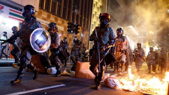 FILE PHOTO: Police pass a burning barricade to break up thousands of anti-government protesters during a march billed as a global