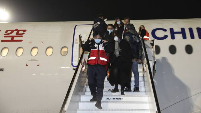 In this photo released by China's Xinhua News Agency, members of a Chinese aid team arrive at Fiumicino Airport in Rome, late Thursday, March 12, 2020. According to Chinese state media, a charter plane carrying members of a medical team and several tons of medical supplies from China arrived in Rome to assist Italy in fighting the coronavirus outbreak. For most people, the new coronavirus causes only mild or moderate symptoms. For some it can cause more severe illness. (Cheng Tingting/Xinhua via AP)