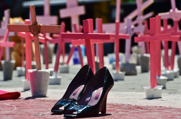 High-heeled shoes from a victim of femicide are pictured next to crosses during a protest against the murder of more than 600 women in the last four years, in Ecatepec, State of Mexico, on March 13 , 2016. AFP PHOTO/RONALDO SCHEMIDT / AFP / RONALDO SCHEMIDT (Photo credit should read RONALDO SCHEMIDT/AFP via Getty Images)