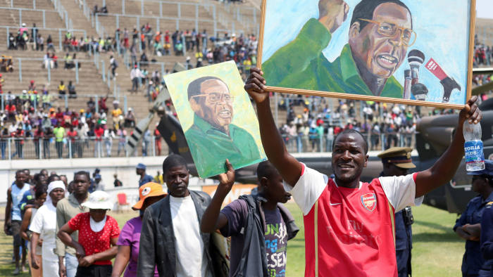 Mourners hold paintings with the face of former Zimbabwean president Robert Mugabe, as they queue to pay their last respects as he lies in state at the at Rufaro stadium, in Mbare, Harare, Zimbabwe, September 13, 2019. REUTERS/Siphiwe Sibeko NO RESALES. NO ARCHIVES TPX IMAGES OF THE DAY