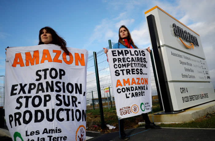 TOPSHOT - ANV-COP 21 (non violent action - Climate Change Conference 21) and Les Amis de la Terre (Friends of the Earth) activists block an Amazon centre in Bretigny-sur-Orge on November 28, 2019, to protest against the company's labour policies and impact on climate change. (Photo by Thomas SAMSON / AFP) (Photo by THOMAS SAMSON/AFP via Getty Images)