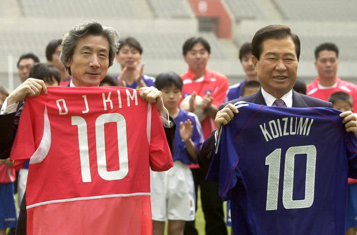 402750 02: Japanese Prime Minister Junichiro Koizumi (L) and South Koreas President Kim Dae-Jung (R) hold national soccer team shirts belonging to South Korea (red) and Japans national soccer team (blue) March 22, 2002 during a visit to Seoul World Cup Stadium. Koizumi and Kim vowed to make their joint hosting of the World Cup this year a stepping stone to long term friendship after decades of animosity. (Pool Photo/Getty Images)