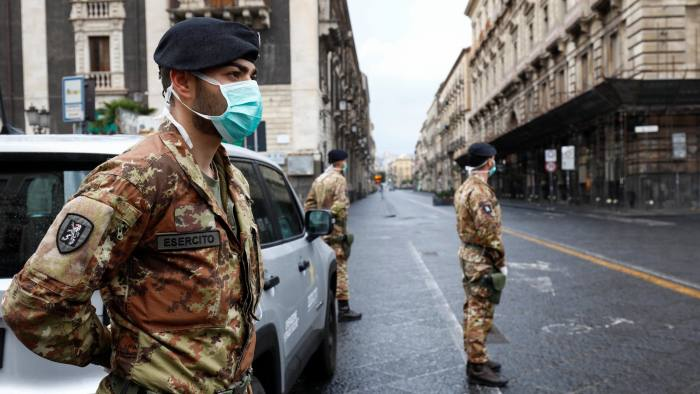 Italian soldiers wearing protective masks work at a roadblock after Italy reinforced the lockdown measures to combat the coronavirus disease (COVID-19) in Catania, Italy March 21, 2020. REUTERS/Antonio Parrinello
