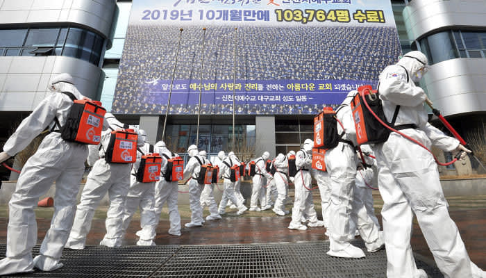 Army soldiers wearing protective suits spray disinfectant to prevent the spread of the coronavirus in front of a branch of the Shincheonji Church of Jesus in Daegu, South Korea, Sunday, March 1, 2020. The coronavirus number of cases shot up in Iran, Italy and South Korea and the spreading outbreak shook the global economy. (Lee Moo-ryul/Newsis via AP)