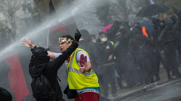 """'Yellow Vest' (gilets jaunes) anti-government movement protester are soaked by a police water canon as he takes part of a nationwide multi-sector strike against the French government's pensions overhaul, on January 11, 2020 in Nantes, western France. - France's government on January 11, 2020, offered a possible compromise to unions waging a crippling, weeks-long transport strike against pension reform, offering to withdraw the most contested proposal that would in effect have raised the retirement age by two years. """"To demonstrate my confidence in the social partners... I am willing to withdraw from the bill the short-term measure I had proposed"""" to set a so-called """"pivot age"""" of 64 with effect from 2027, Prime Minister Edouard Philippe wrote in a letter to union leaders a day after they met seeking to end the labour action, now in its 38th day. (Photo by Loic VENANCE / AFP) (Photo by LOIC VENANCE/AFP via Getty Images)"""