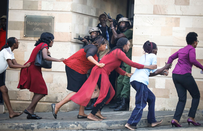 Mandatory Credit: Photo by DAI KUROKAWA/EPA-EFE/REX/Shutterstock (10061640bz)Women are evacuated out of the scene as security officers search for attackers during an ongoing gunfire and explosions in Nairobi, Kenya, 15 January 2019. According to reports, a large explosion and sustained gunfire sent workers fleeing for their lives at an upscale hotel and office complex in the Kenyan capital of Nairobi.Explosion and gunfire in Nairobi, Kenya - 15 Jan 2019