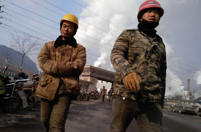 TANGSHAN, CHINA - JANUARY 20: Workers walk out the main gate of Qian'an steelworks of Shougang Corporation on January 20, 2016 in Tangshan, China. Shougang Corporation is one of the most largest steel enterprise in China. Tangshan is the largest steel manufacturing city in China. Shougang Corporation had moved out all steelworks from Beijing before 2008 due to serious air pollution. (Photo by Xiaolu Chu/Getty Images)
