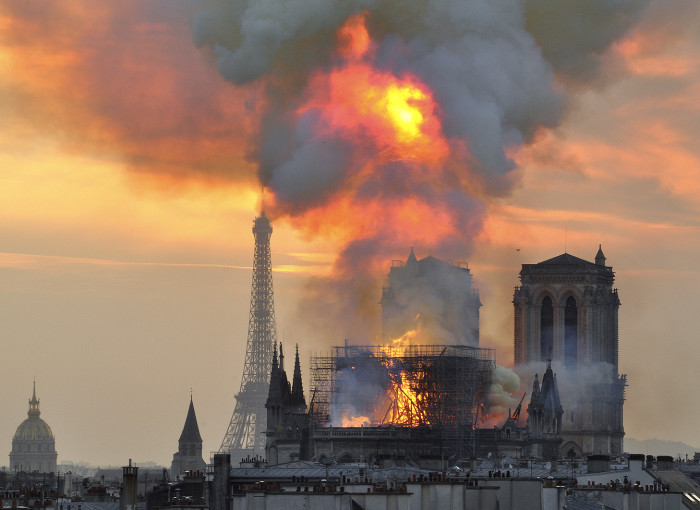 "In this image made available on Tuesday April 16, 2019 flames and smoke rise from the blaze at Notre Dame cathedral in Paris, Monday, April 15, 2019. An inferno that raged through Notre Dame Cathedral for more than 12 hours destroyed its spire and its roof but spared its twin medieval bell towers, and a frantic rescue effort saved the monument's ""most precious treasures,"" including the Crown of Thorns purportedly worn by Jesus, officials said Tuesday. (AP Photo/Thierry Mallet)"