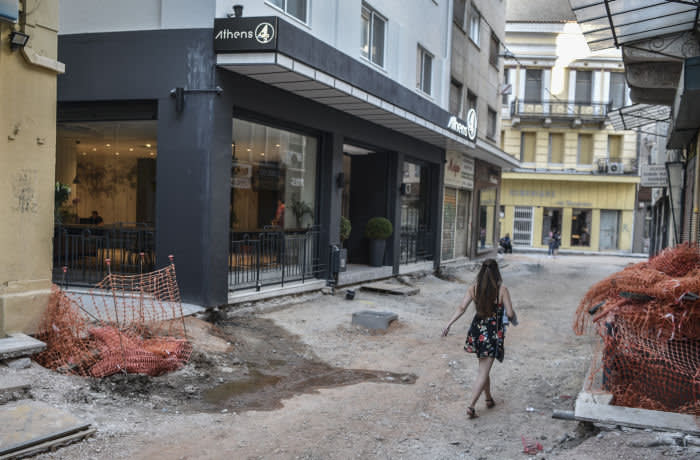 "A woman walks past a luxury hotel and construction works turing the street into a pedestrian zone, in the historical center of Athens on May 30, 2019. - Battered by the crisis that ravaged the rest of the country, Athens will have a new mayor on June 2, 2019 and a challenge to push back the results of a long recession. According to outgoing deputy Athens mayor Lefteris Papagiannakis, the number of visitors more than doubled in recent years owing to a certain ""notoriety"" attached to the city's image. There has also been an expansion of street art and a proliferation of socio-cultural centers -- meeting points for artists, professionals and refugees -- that arose in response to the collapse of state-funded welfare. (Photo by LOUISA GOULIAMAKI / AFP) (Photo credit should read LOUISA GOULIAMAKI/AFP via Getty Images)"