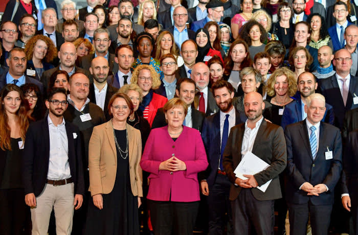 German Chancellor Angela Merkel (C) poses for group pictures with German State Minister for Migration, Refugees and Integration Annette Widmann-Mauz and during the awards ceremony of the National integration prize on October 29, 2018 at the Chancellery in Berlin. - Earlier in the day Merkel had announced she will quit as German chancellor when her mandate ends in 2021, as she sought to draw a line under a series of political crises that have rocked her fragile coalition. (Photo by Tobias SCHWARZ / AFP) (Photo credit should read TOBIAS SCHWARZ/AFP via Getty Images)
