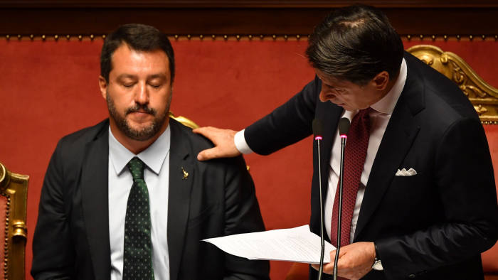 "TOPSHOT - Italian Prime Minister Giuseppe Conte (R) touches Deputy Prime Minister and Interior Minister Matteo Salvini's shoulder as he delivers a speech at the Italian Senate, in Rome, on August 20, 2019, as the country faces a political crisis. - Italy's Premier Conte says to offer resignation during his speech at the Senate after calling Italy's far-right Interior Minister Matteo Salvini ""irresponsible"" to spark a political crisis by pulling the plug on the governing coalition. (Photo by Andreas SOLARO / AFP)ANDREAS SOLARO/AFP/Getty Images"