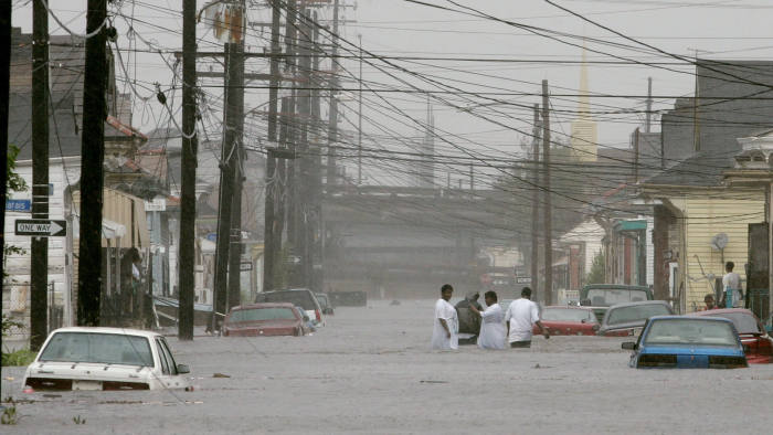 NEW ORLEANS - AUGUST 28: People walk down a flooded street after Hurricane Katrina hit the area August 29, 2005 in New Orleans, Louisiana. Katrina was down graded to a category 4 storm as it approached New Orleans. (Photo by Mark Wilson/Getty Images)