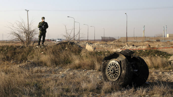 A police officer stands guard as debris is seen from an Ukrainian plane which crashed in Shahedshahr, southwest of the capital Tehran, Iran, Wednesday, Jan. 8, 2020. A Ukrainian airplane carrying 176 people crashed on Wednesday shortly after takeoff from Tehran's main airport, killing all onboard. (AP Photo/Ebrahim Noroozi)