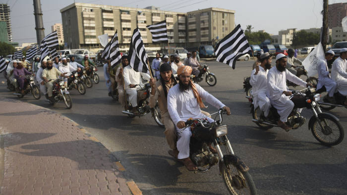 Activists of Jamiat Ulema-e Islam (JUI) carry party flags as they march in a rally in Karachion October 25, 2019. - JUI chief Maulana Fazal-ur-Rehman had announced that the party will begin its anti-government 'Azadi March' on October 27. (Photo by RIZWAN TABASSUM / AFP)