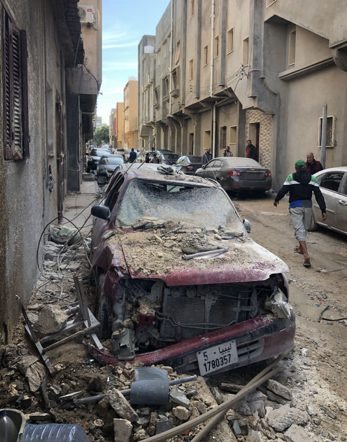 Libya Andrew England A man walks past a car that was damaged after rocket struck a house in the southern neighbourhood of Tripoli