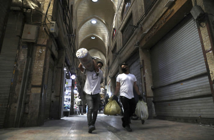 In this Tuesday, March 17, 2020, photo, men carry their goods through mostly closed Tehran's Grand Bazaar, Iran. The new coronavirus ravaging Iran is cutting into celebrations marking the Persian New Year, known as Nowruz. (AP Photo/Vahid Salemi)